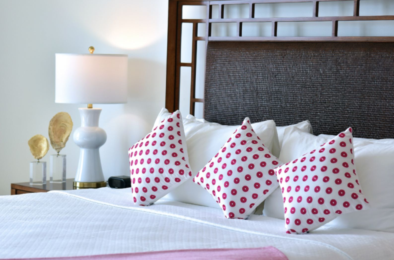 The tasteful decor at the Coral Beach Club showing bed with pink dotted cushions