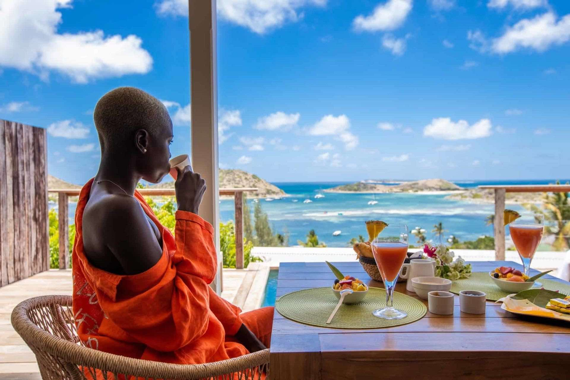 Woman sipping cofffee on balcony overlooking ocean at le-karibuni-boutique-hotels in St MarAtin