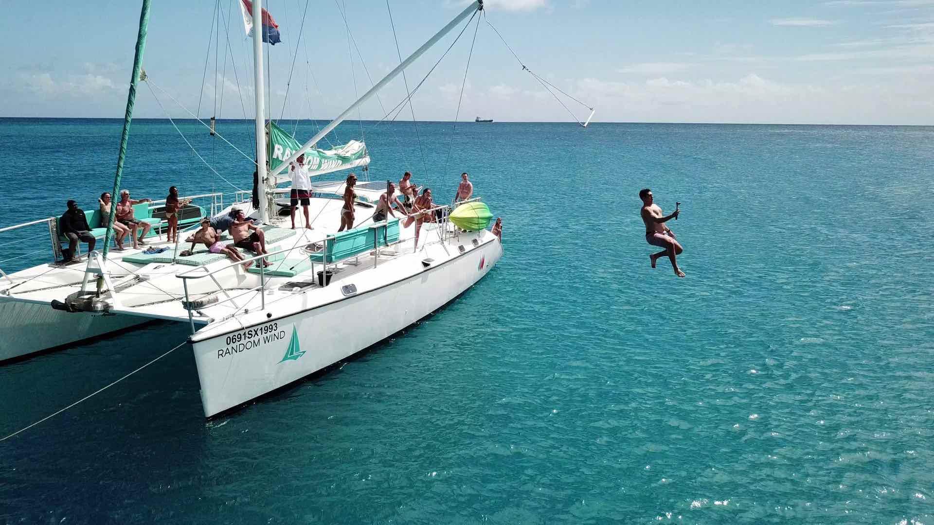 The Tarzan swing with many jumping in water aboard Random Wind Charters yacht